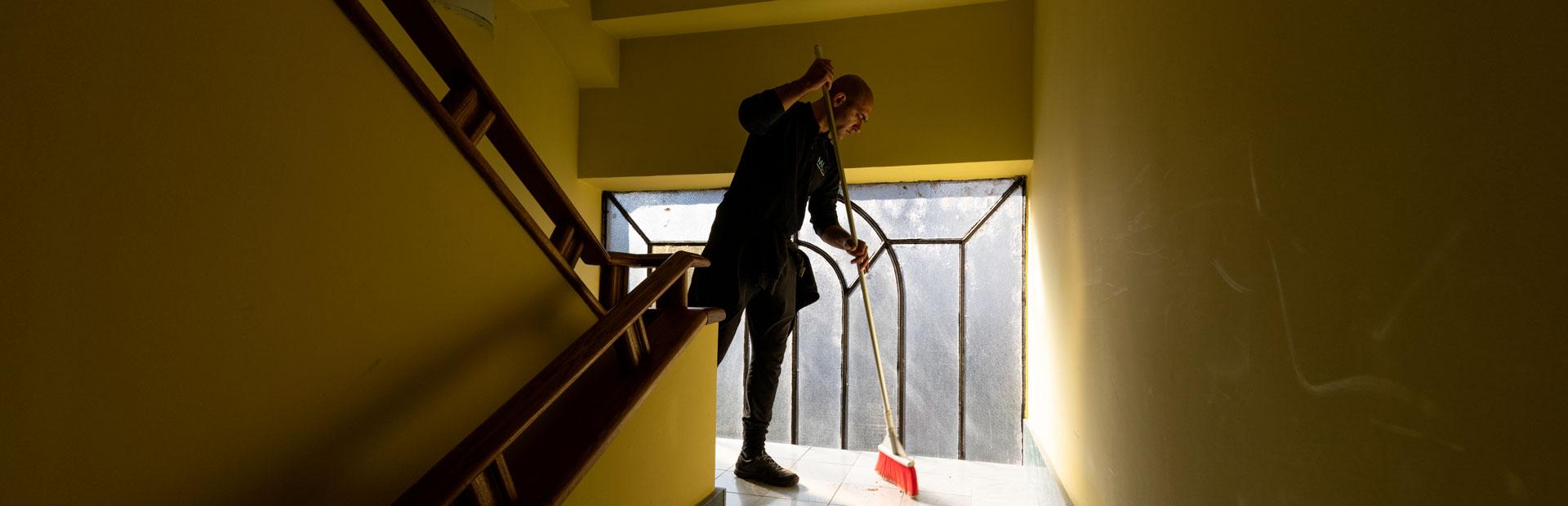 Particolare dell'azione di un'impresa di pulizie a Torino. L'addetto con una scopa rossa pulisce il pavimento in piastrelle del pianerottolo di una scala condominiale. Le pareti sono di colore giallo oro e il mancorrente è in legno scuro. Sullo sfondo si trova un'ampia vetrata.