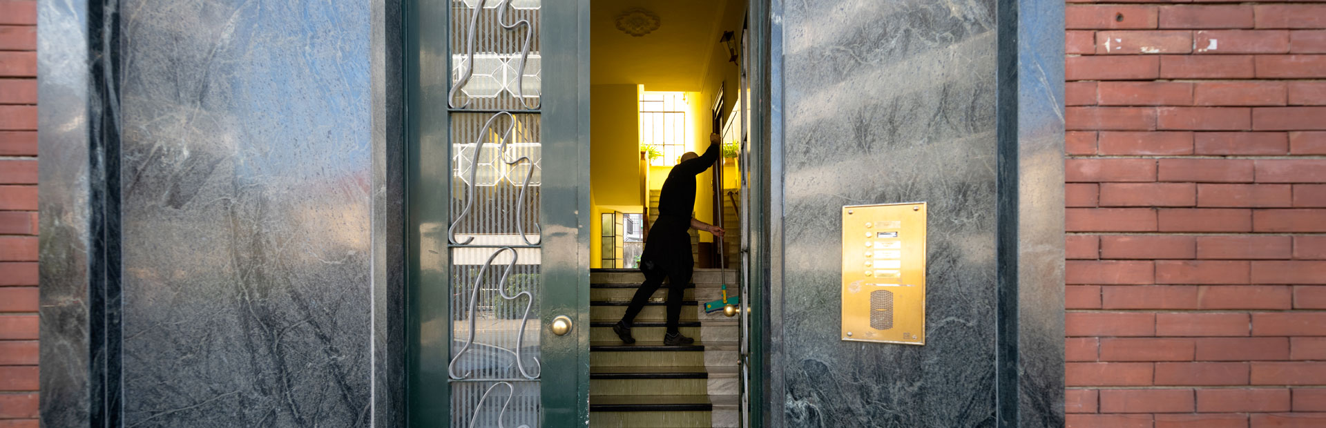 Esempio di pulizie in interni di condomini. L'addetto scopa la scala nell'androne di uno stabile, inquadrato dal portone a vetri semiaperto che è contornato da pregiato marmo verde. Il citofono dorato si trova a destra dell'ingresso.